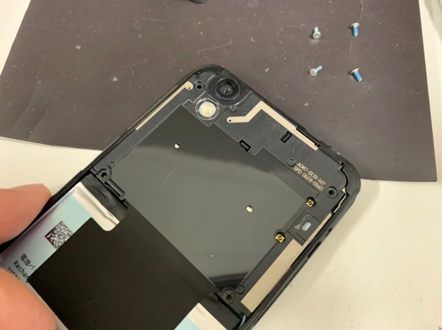 プラスチックパーツを止めたネジを外しているAndroid One S3