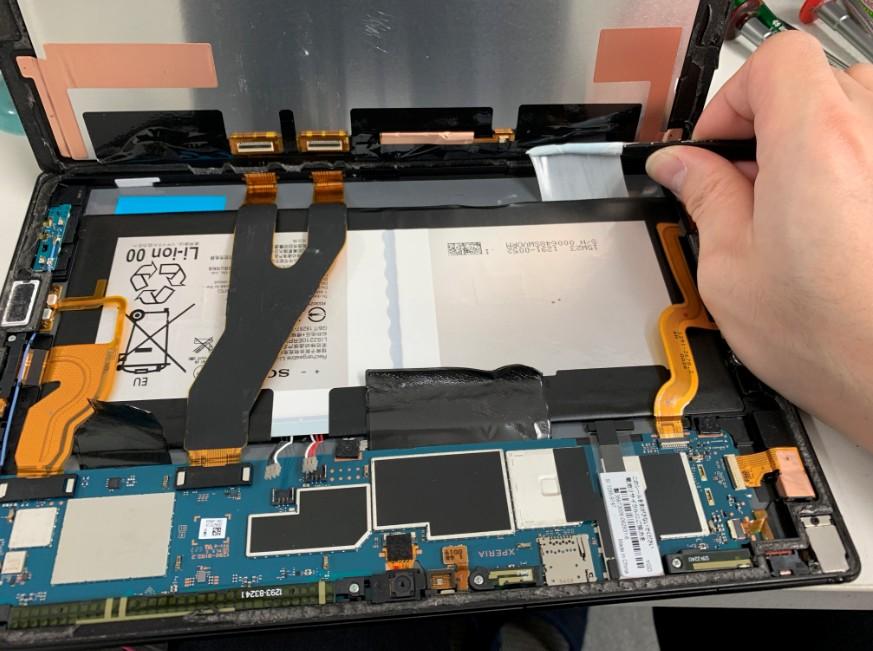 バッテリーを固定している粘着テープを剥がしているXperia Z4 Tablet