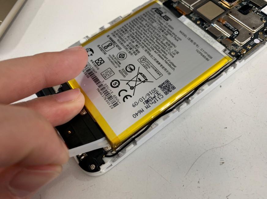 もう一本のバッテリーシールを剥がしているZenfoma3Max(ZC520TL)