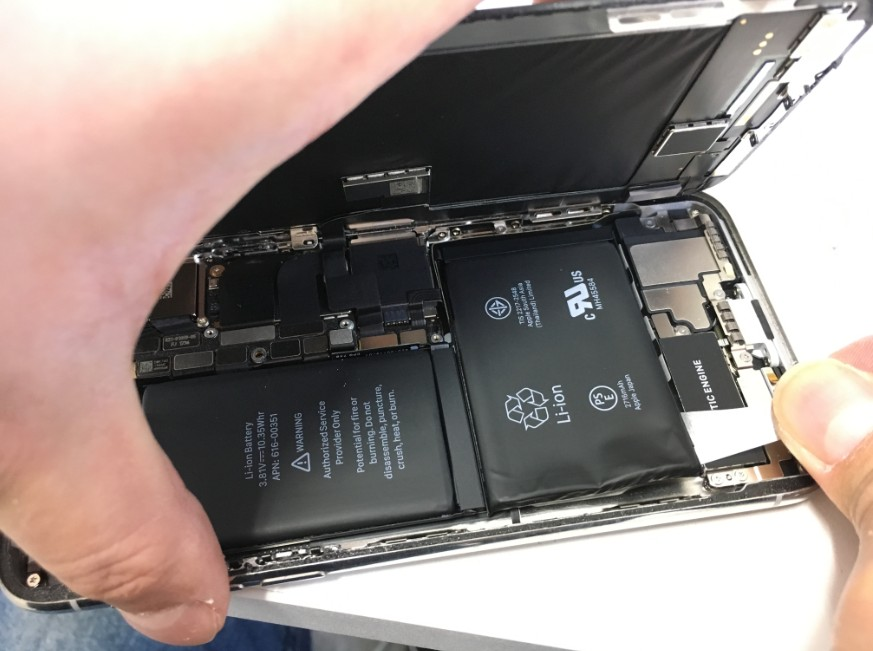 バッテリー固定シールを剥がしているiPhoneX