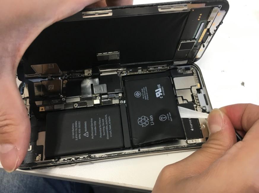 バッテリー固定シール本体下部真ん中のシールを引っ張っているiPhoneX