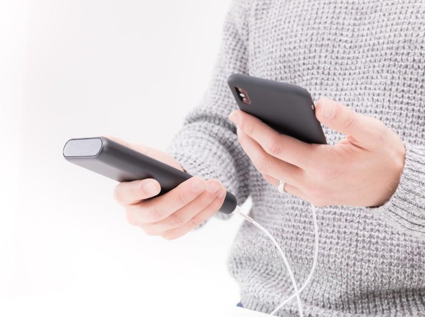 スマートフォンを充電しながら使用している人