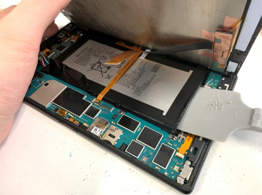 ヘラでバッテリーを剥がしているXperia Z3 Tablet Compact