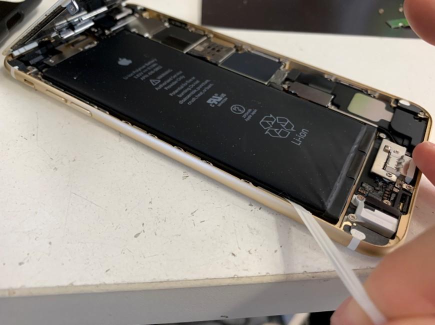 バッテリー固定シールを引っ張っているiPhone6Plus