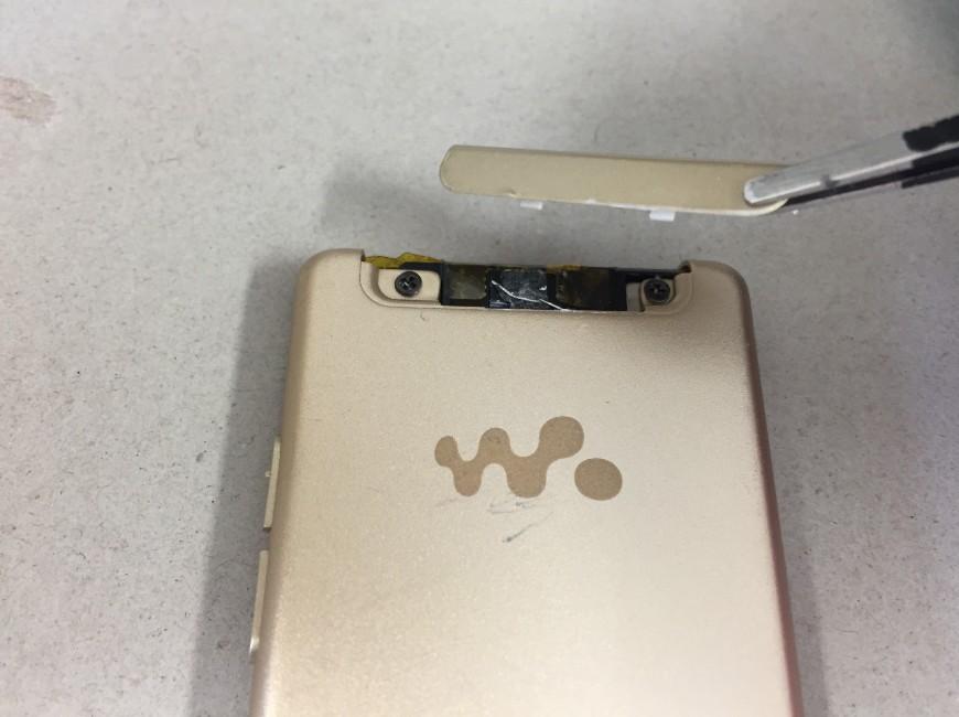 背面の本体上部のプラスチックパーツを剥がしているウォークマン NW-S774