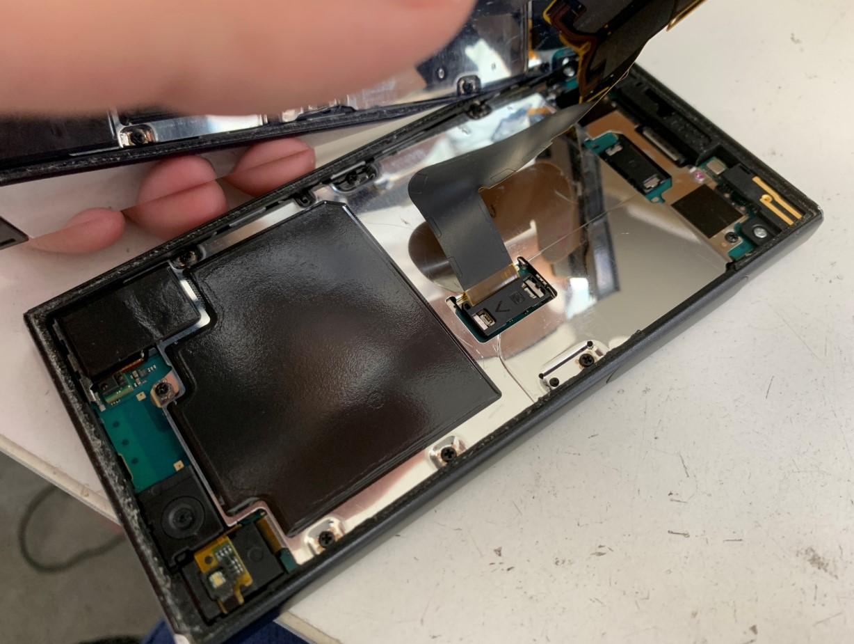 画面を持ち上げてコネクタを外そうとしているXperia XZ1 Compact(SO-02K)