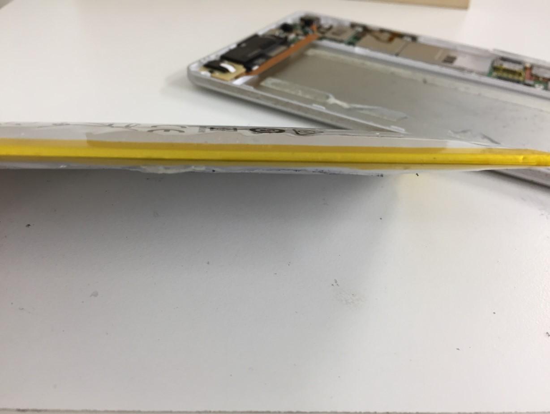膨張したバッテリーを取り出して横から見ているd-02h(ドコモタブレット)