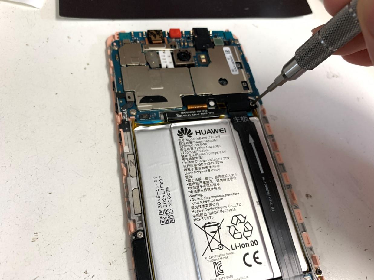 バッテリーコネクタを止めているプレートのネジを外しているHUAWEI Mate S