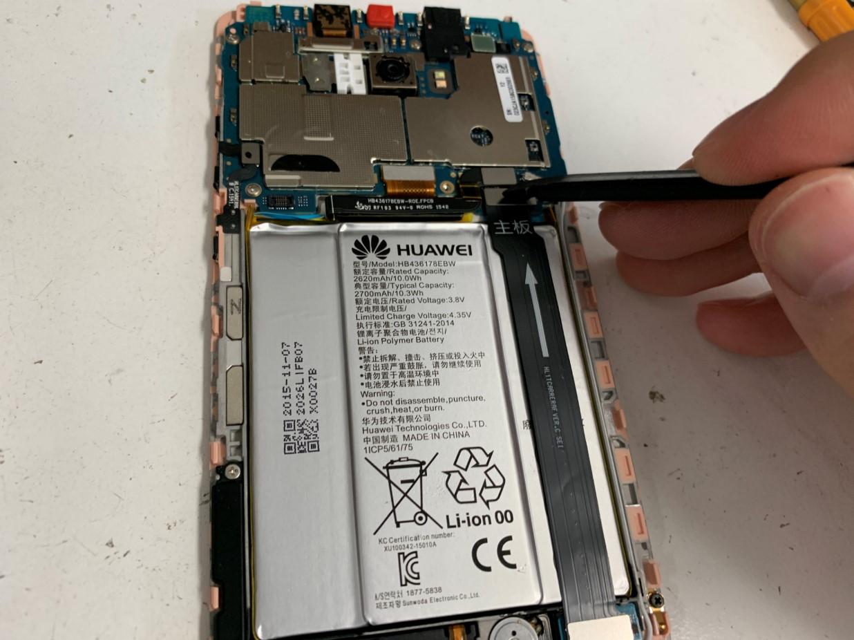 バッテリーコネクタをヘラで外しているHUAWEI Mate S