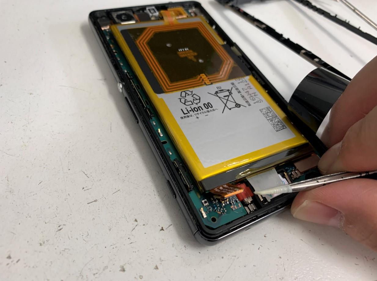 バッテリー固定シールを剥がしているXperia A4(SO-04G)