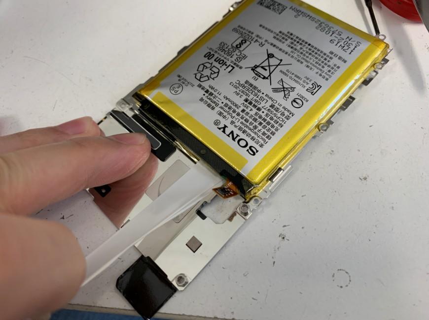 バッテリー固定シールを引っ張って剥がしているXperiaXZs