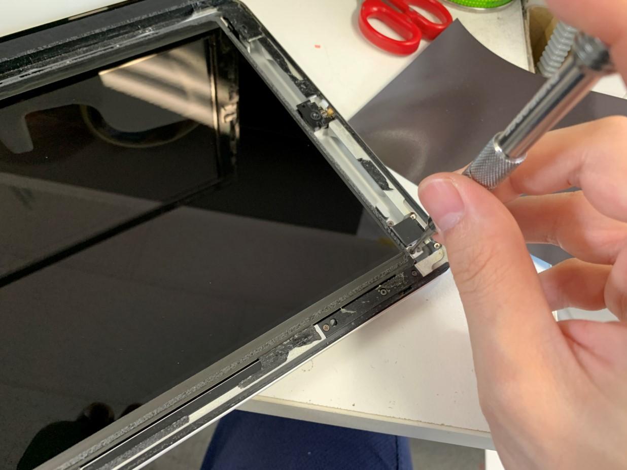 液晶画面を固定しているネジを外しているiPad第3世代