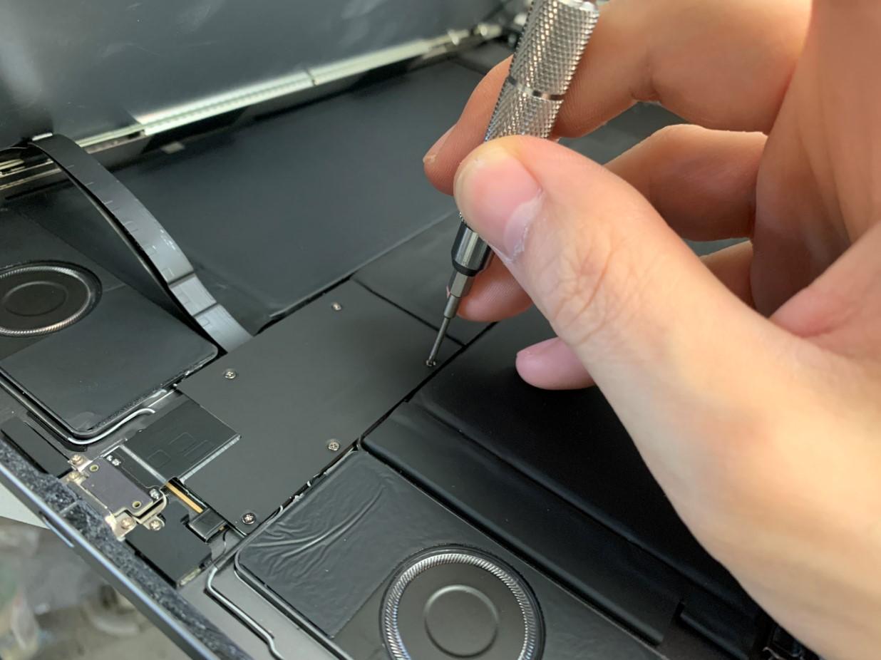 液晶画面のコネクタを止めたプレートのネジを外しているiPadPro 12.9 第4世代