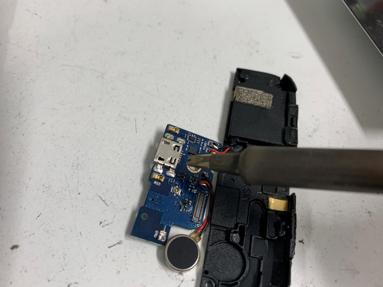 はんだ小手で充電口部分を接続しているOUKITEL(S65)