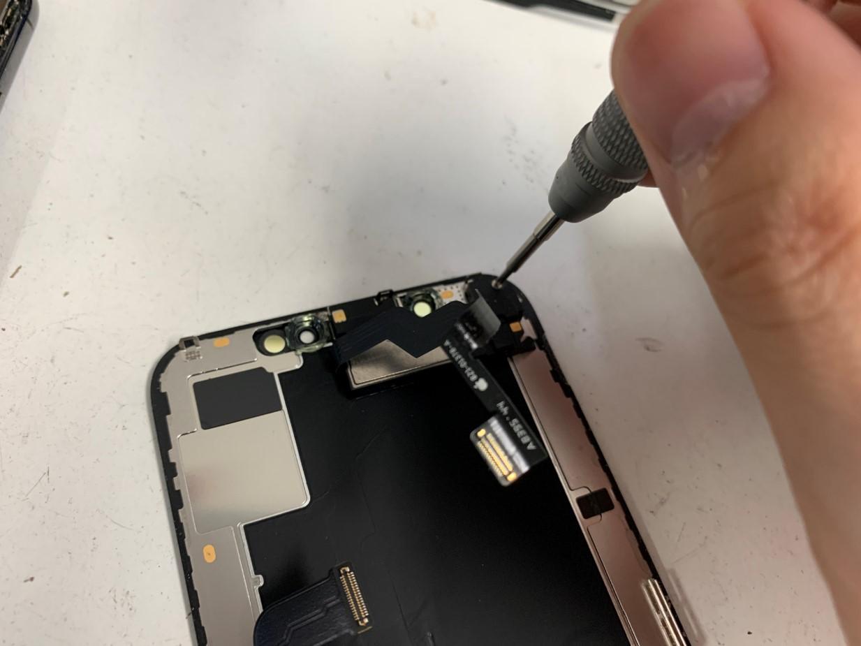 画面上のFaceIDセンサーのネジを外しているiPhoneXS