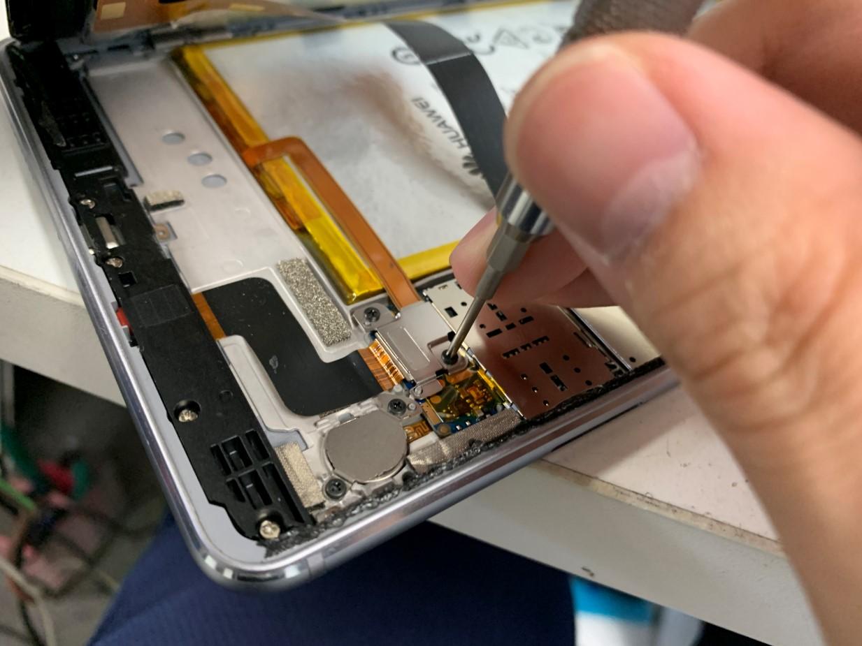 バッテリーのコネクタを止めたプレートをネジを外そうとしているMediaPad M3 lite 8