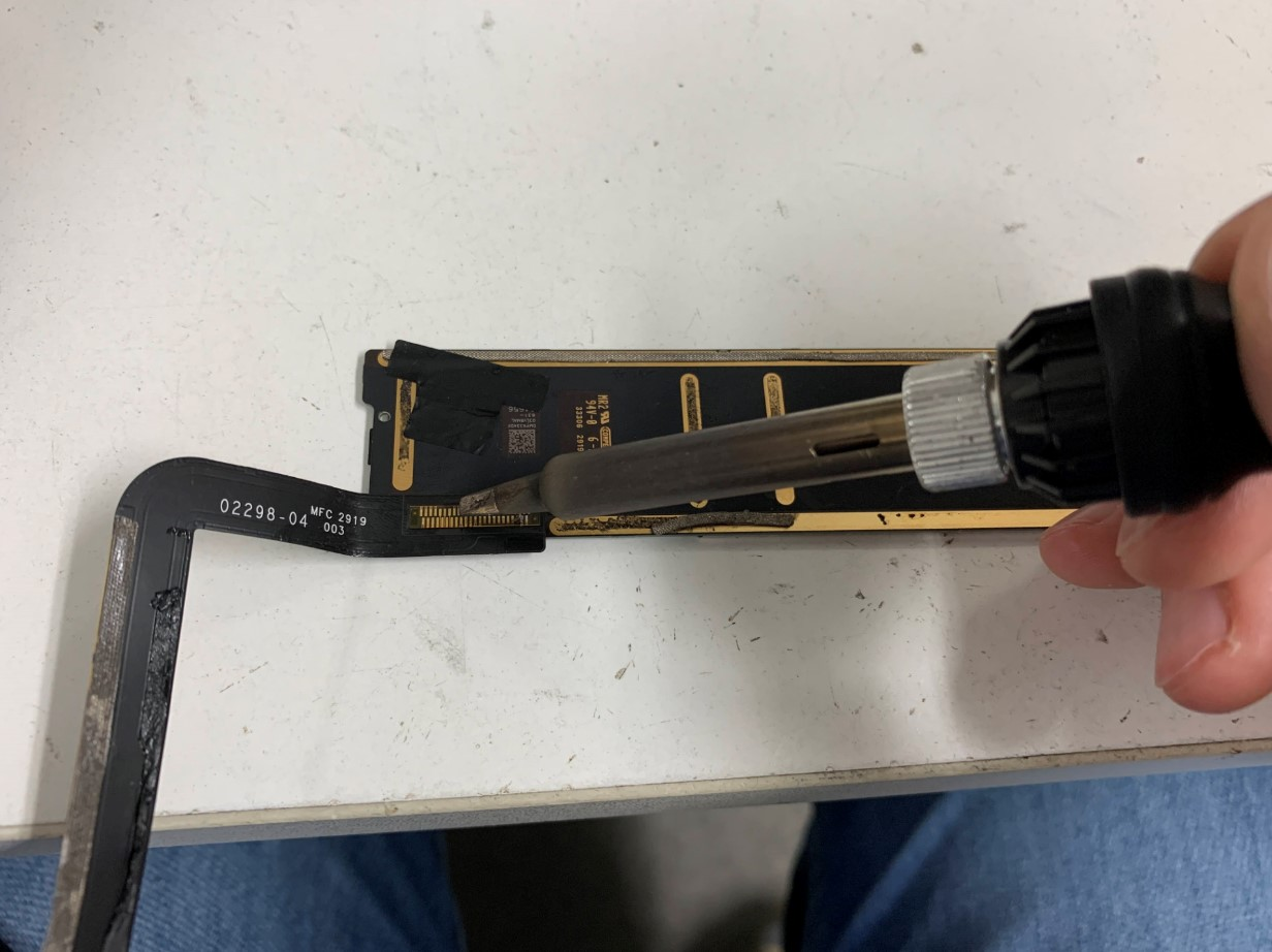 はんだを使って充電口部分を剥がしているiPad第7世代