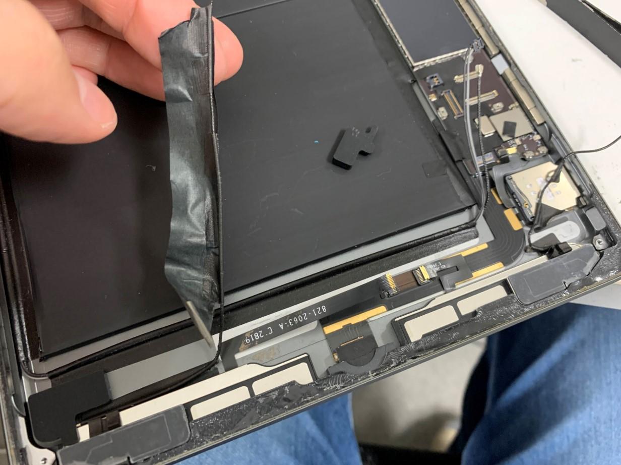 本体下部の絶縁テープを剥がしているiPad第7世代