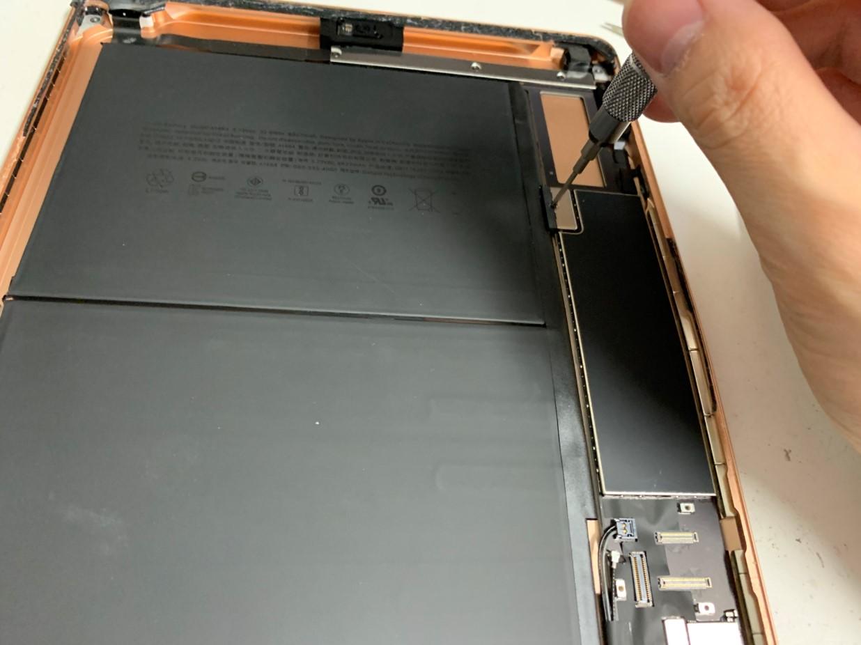 バッテリーコネクタ部分のネジを外そうとしているiPad 第7世代