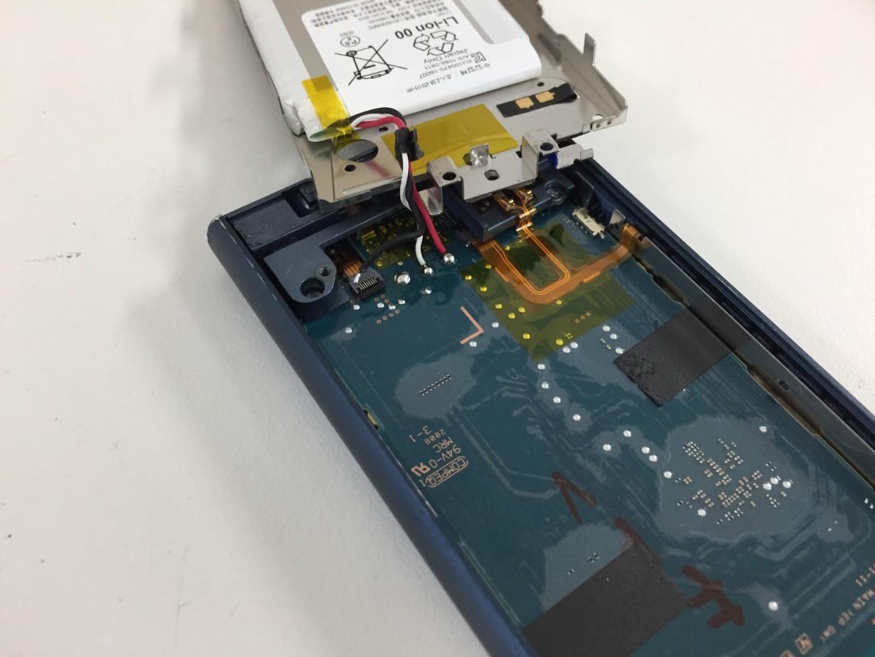 はんだ小手でバッテリーを本体から外そうとしているウォークマン NW-A106