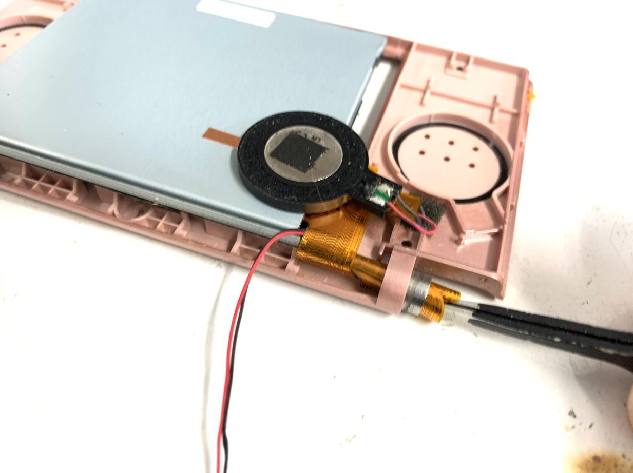 ケーブルを丸めて本体フレームから上液晶画面を取り出そうとしているDS lite