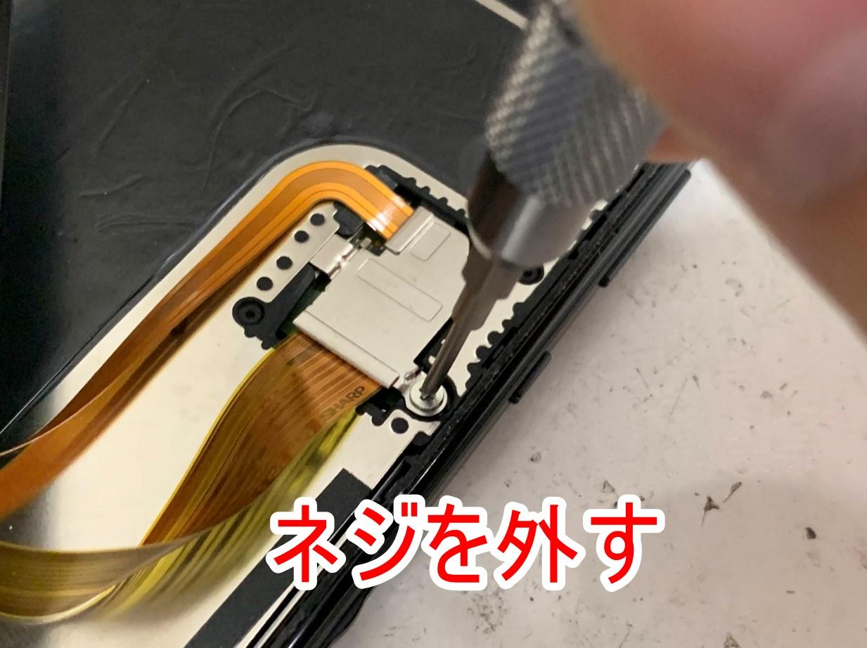 コネクタを止めた銀板のネジを外しているAQUOS sense4