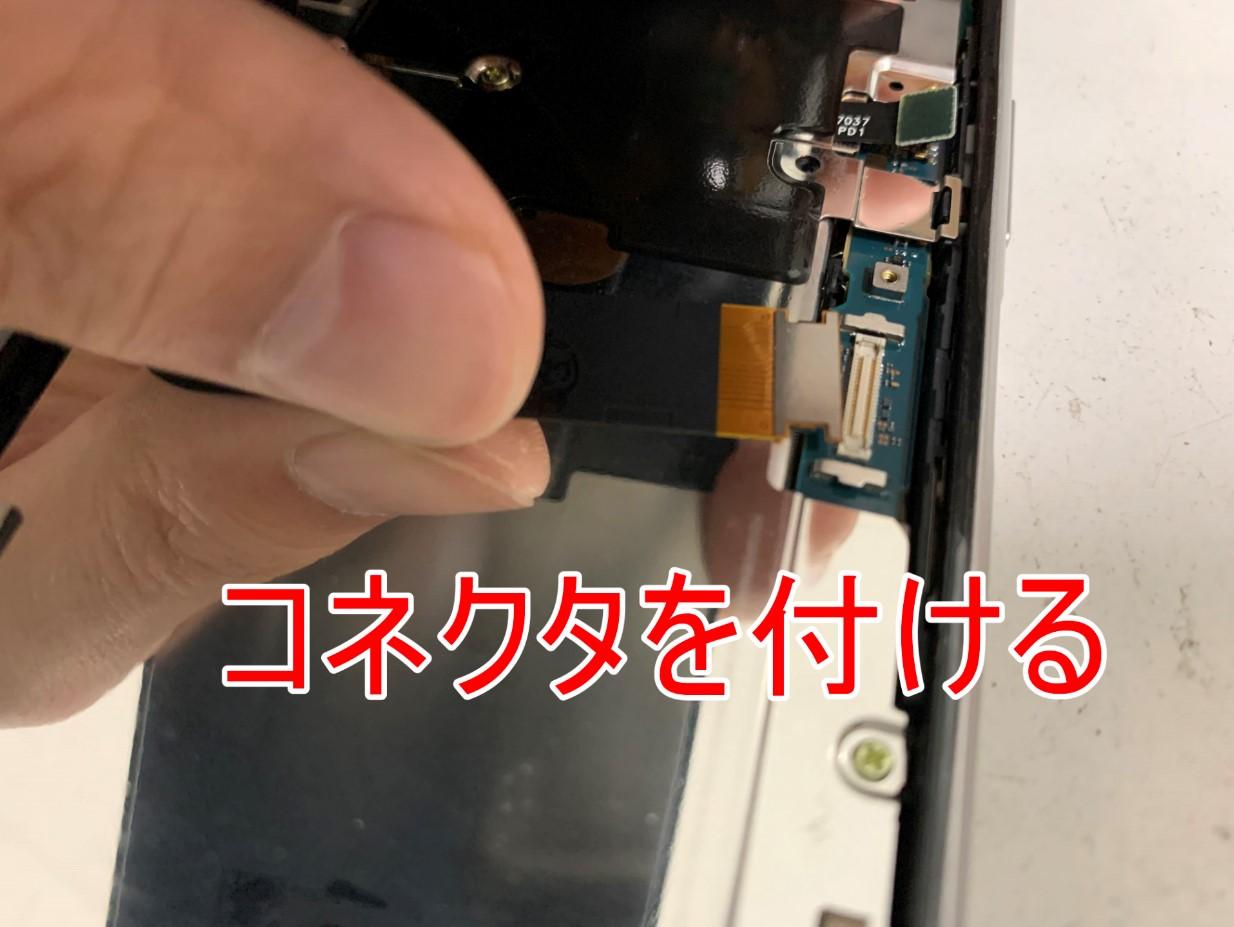新しい画面パーツのコネクタを基板に接続しようとしているXperia 8