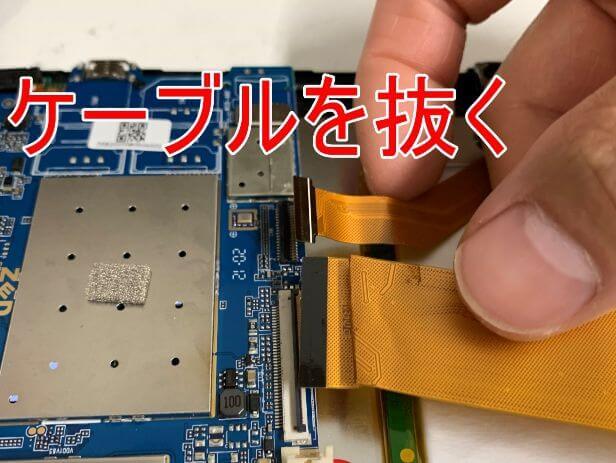 基板に接続されたケーブルを抜いているDragon Touch Max10