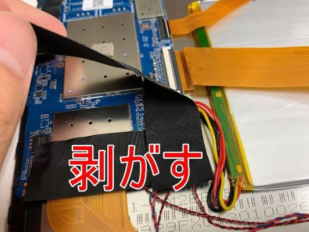 基板を覆った絶縁テープを剥がしているDragon Touch Max10