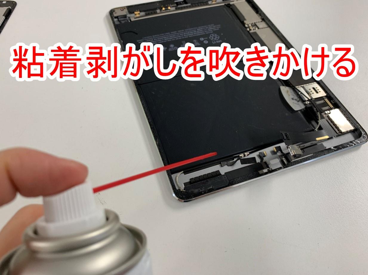 バッテリーに粘着剥がしを吹きかけているiPad Air2