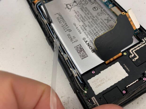バッテリー固定シールを引っ張っているXperia1