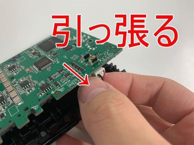 バッテリーコネクタをつまんで引っ張っているヘッドホンアンプPHA-3