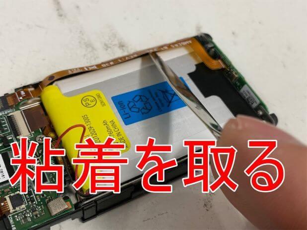 バッテリーに接着されたボリュームボタンケーブルを剥がしているNW-S315