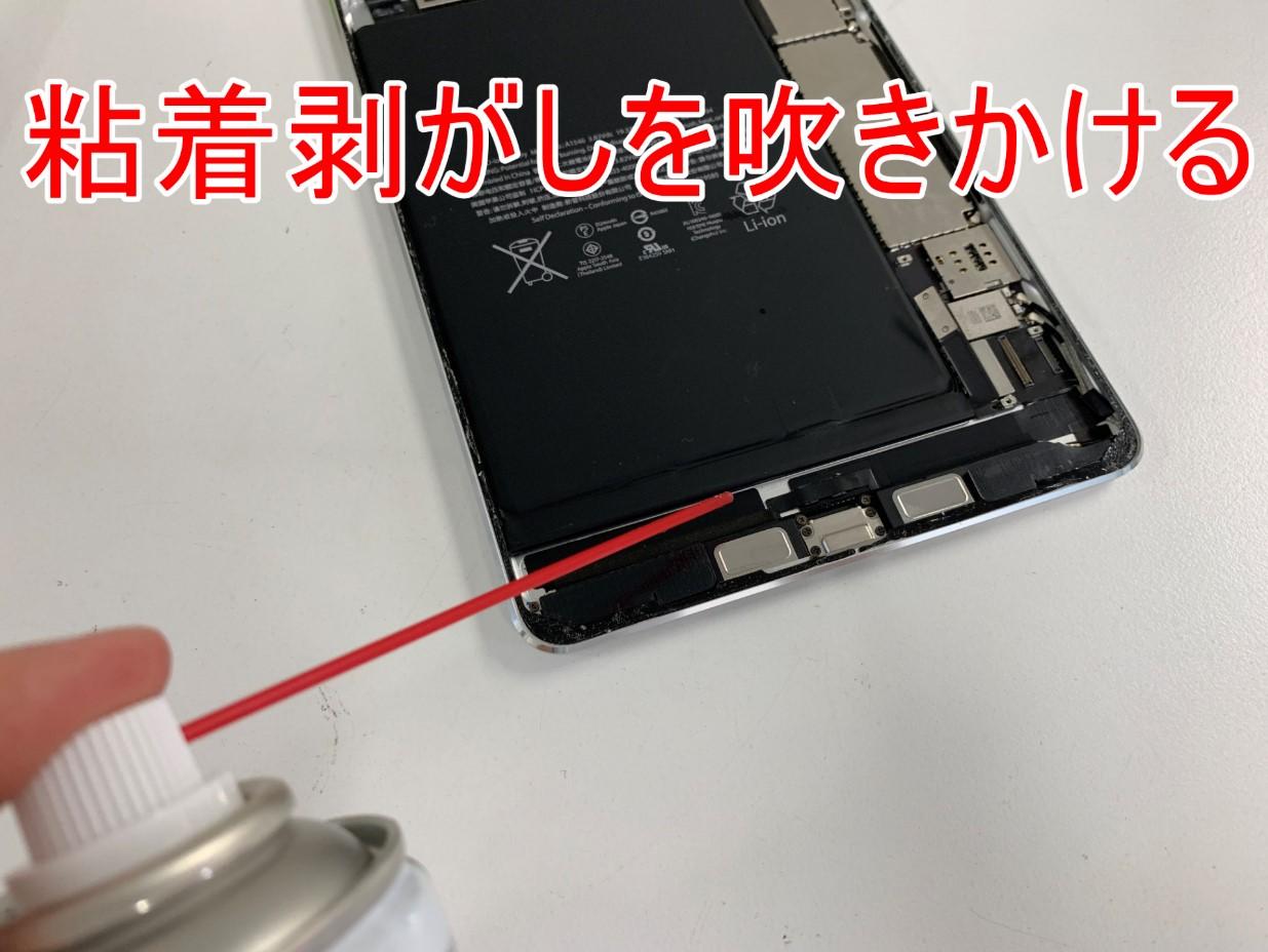 バッテリーと本体の間に粘着剥がしを吹きかけているiPad mini4
