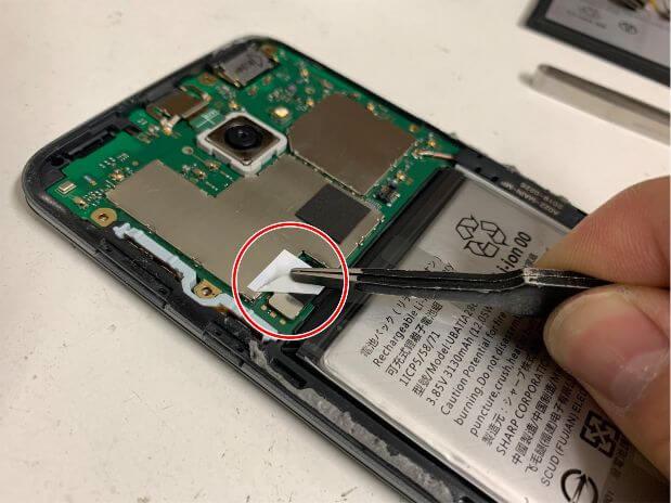 バッテリーコネクタを隠したテープを剥がしているAQUOS zero